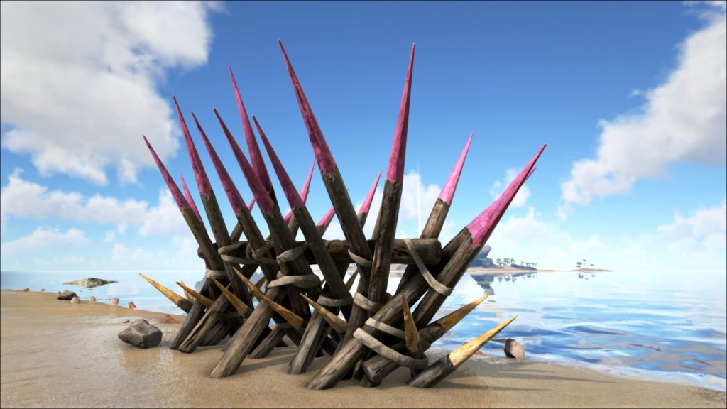 Large wooden defensive spikes on a beach.